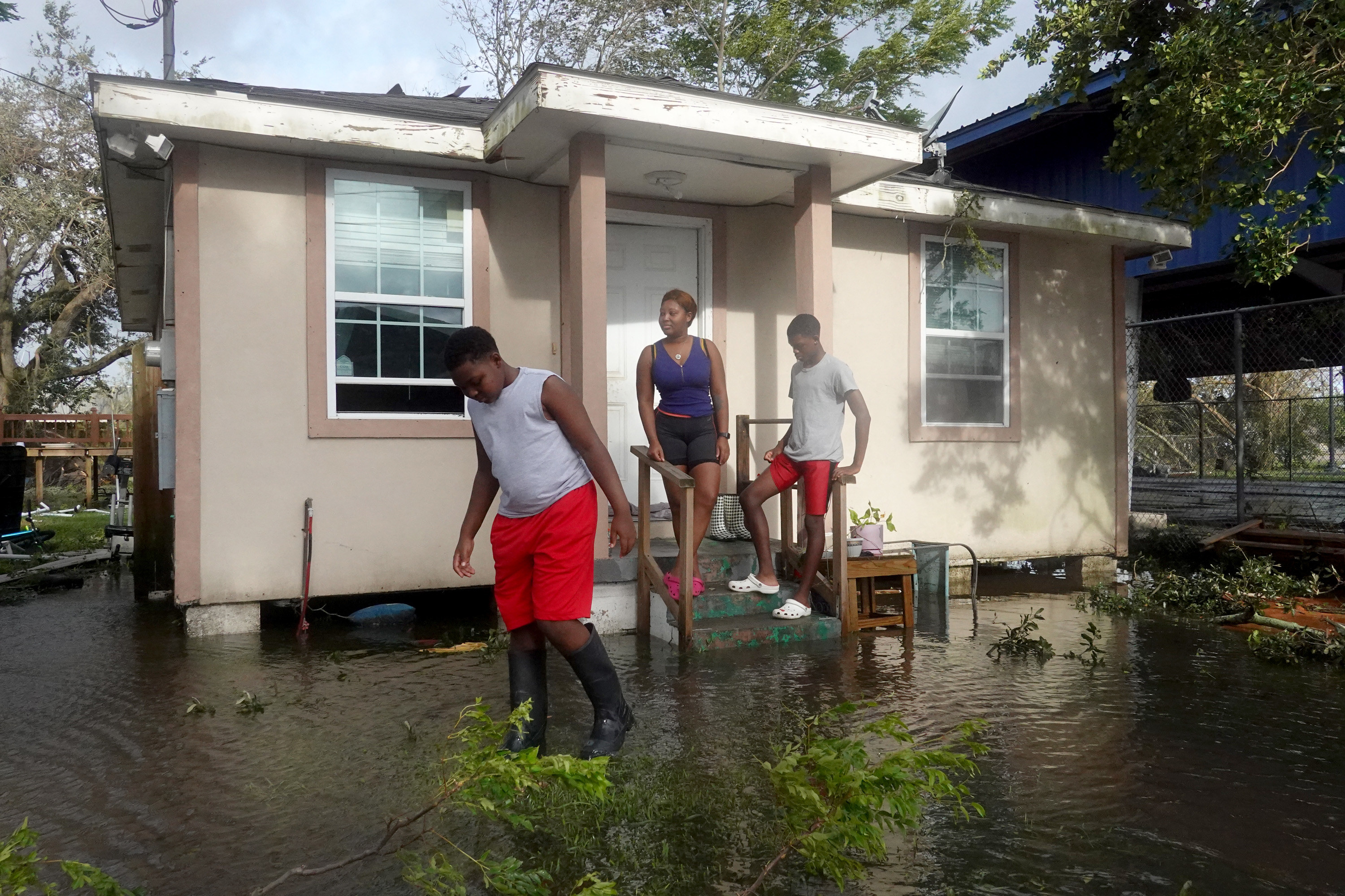 Michelle Washington and her sons Kendrick and Kayden check out damage to their home in the aftermath of Hurricane Ida