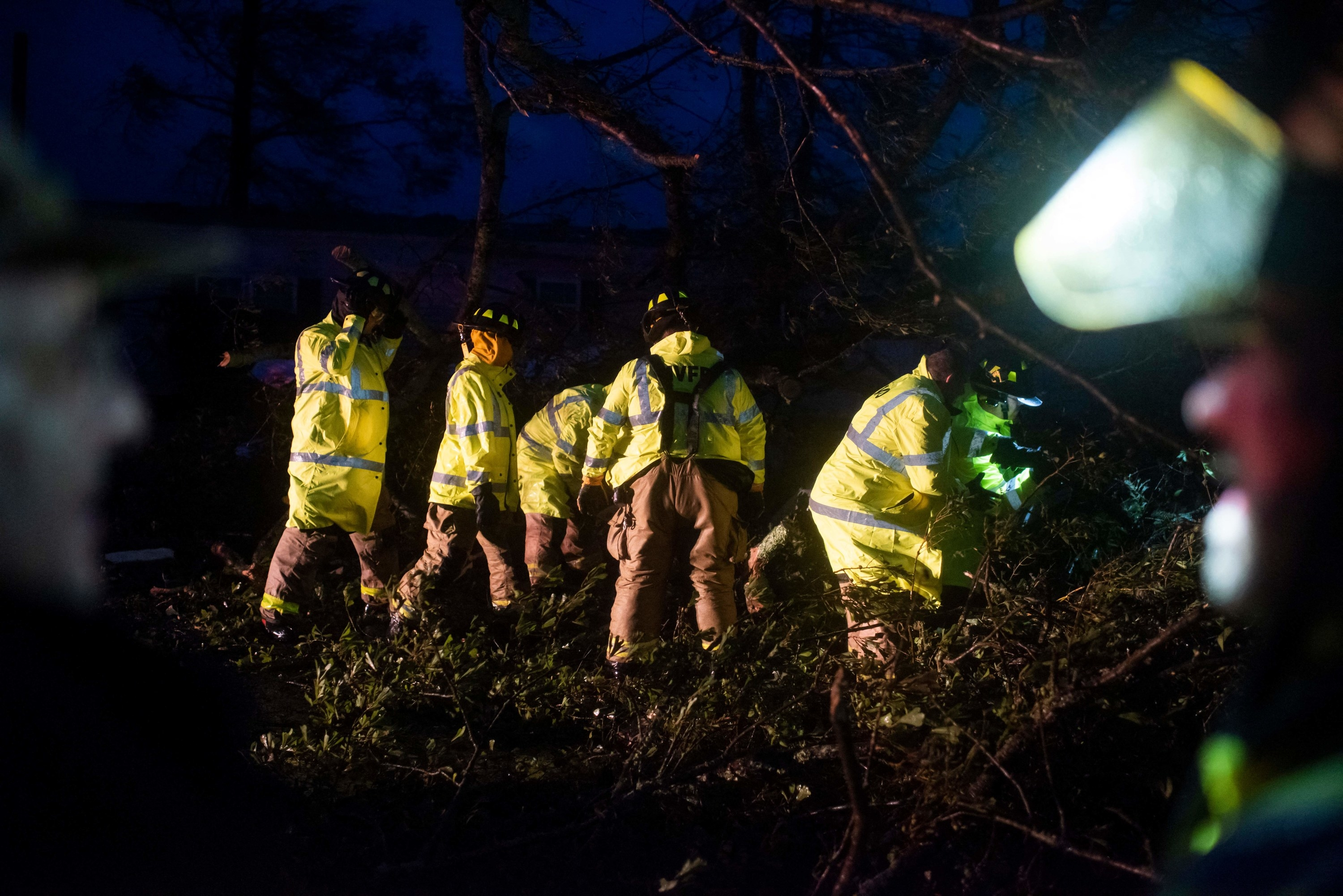 Firefighters cut through trees on the road