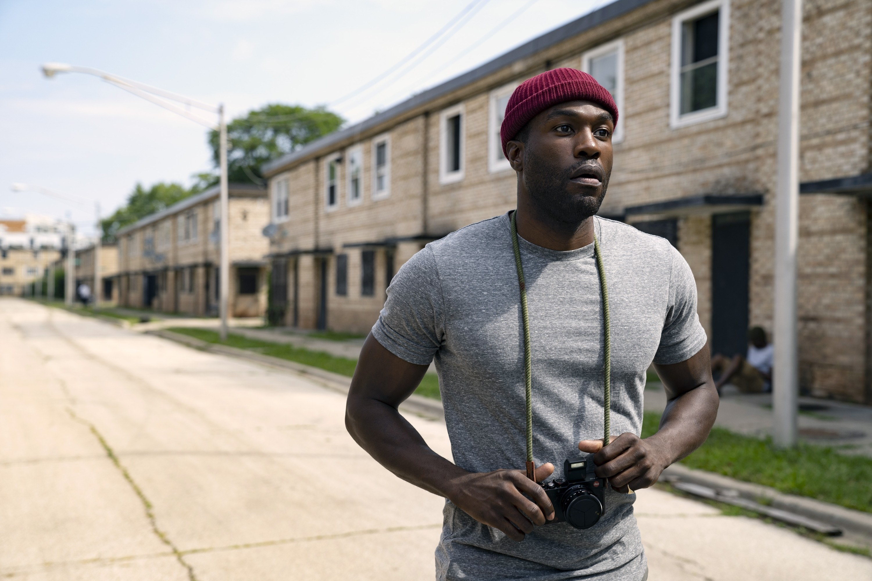 Anthony, walking through an abandoned neighborhood, wearing a camera around his neck