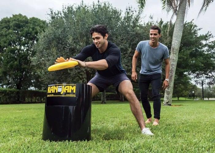 a model slapping a yellow frisbee into a black Kan Jam bin