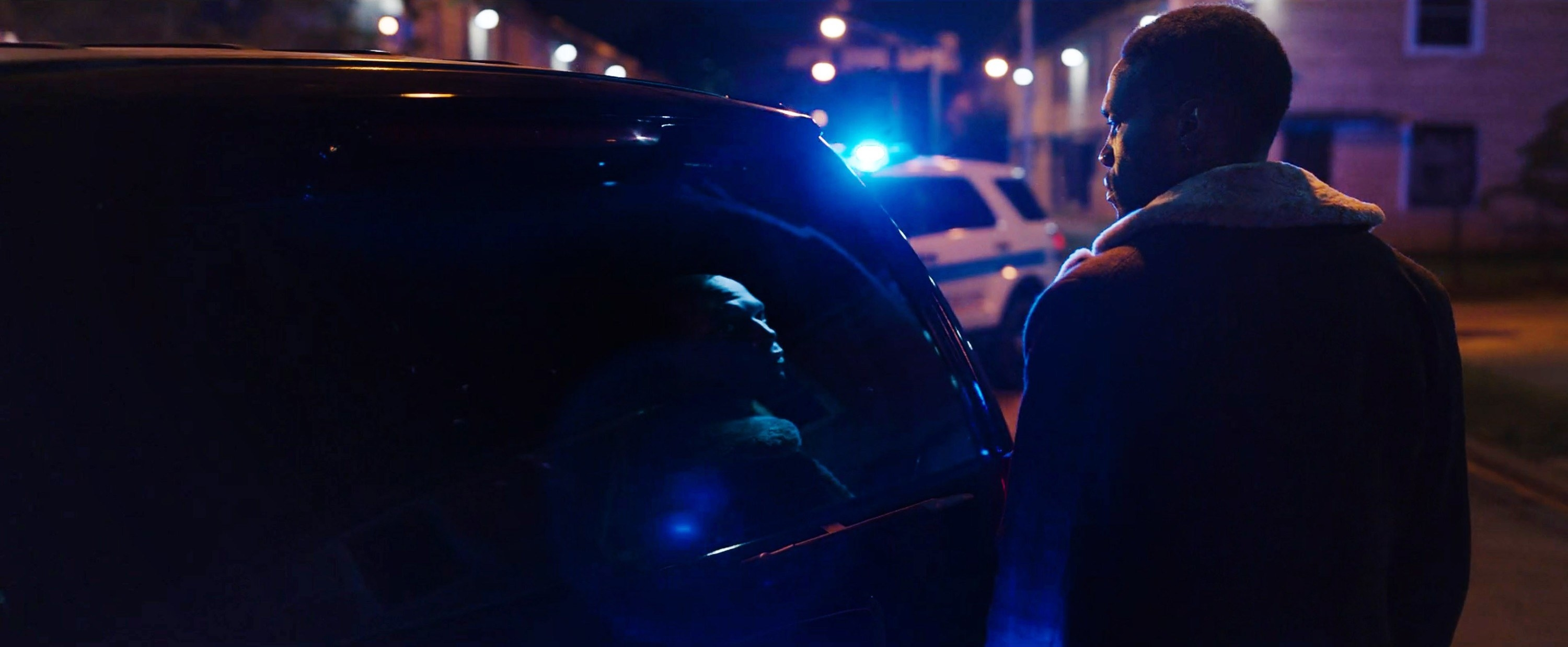 Candyman approaching a police vehicle at night