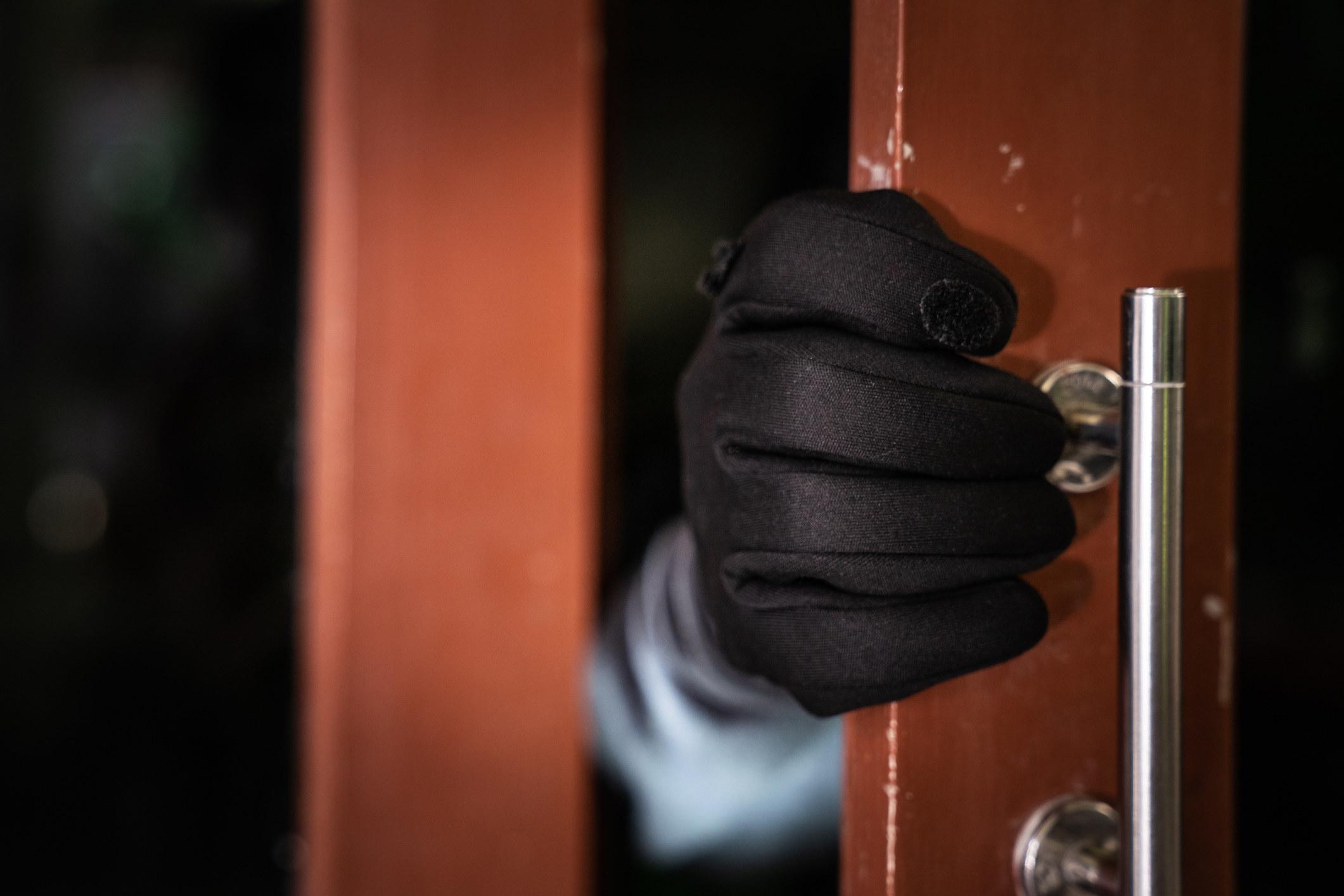 A masked burglar breaks into someone's home door