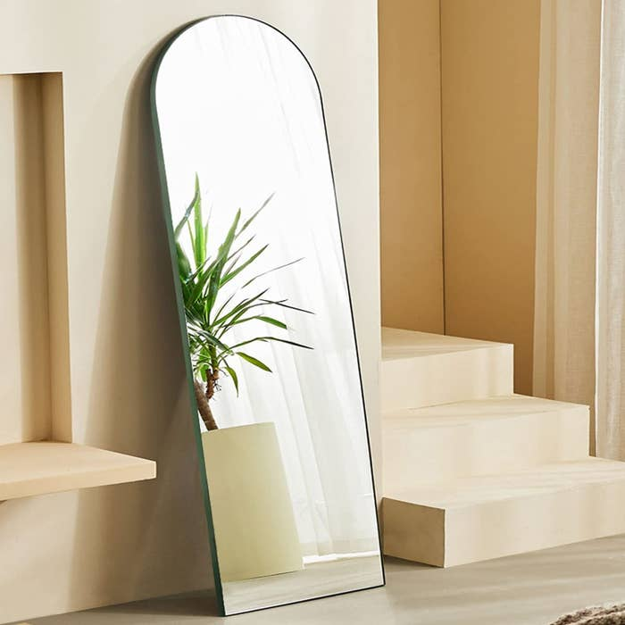 full length mirror with arch at top that's leaning against a wall and has a green outer frame