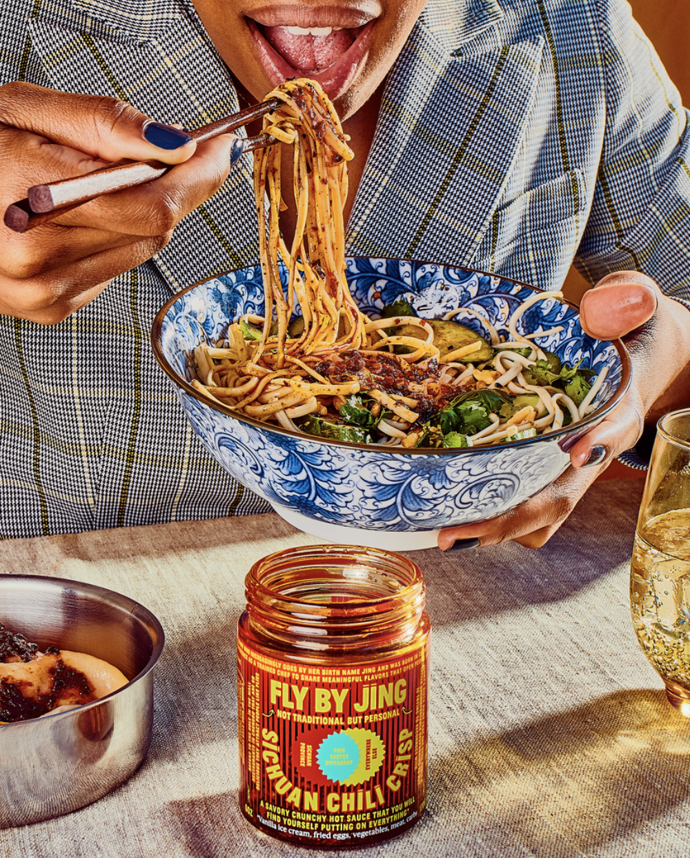 Model eating noodles with Fly BY Jing Sichuan Chili Crisp sauce