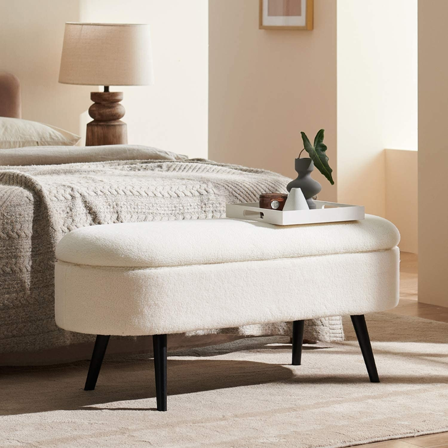 plush bench ottoman with black legs at an angle. it has a removable top and is placed at the foot of a bed.