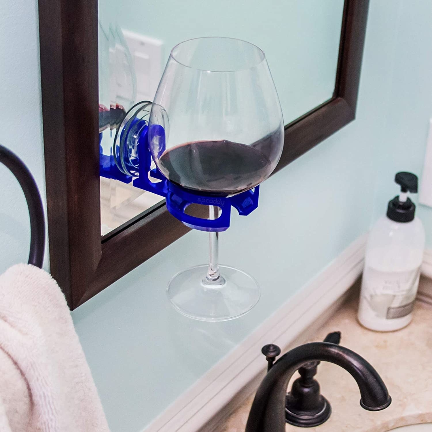 The holder attached to a mirror with a wine glass in it