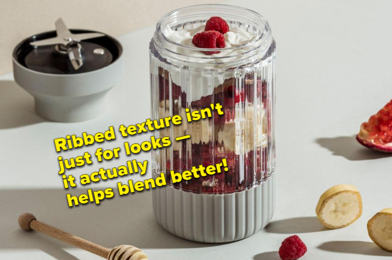 The blender jar filled with berries, yogurt, and other fruit