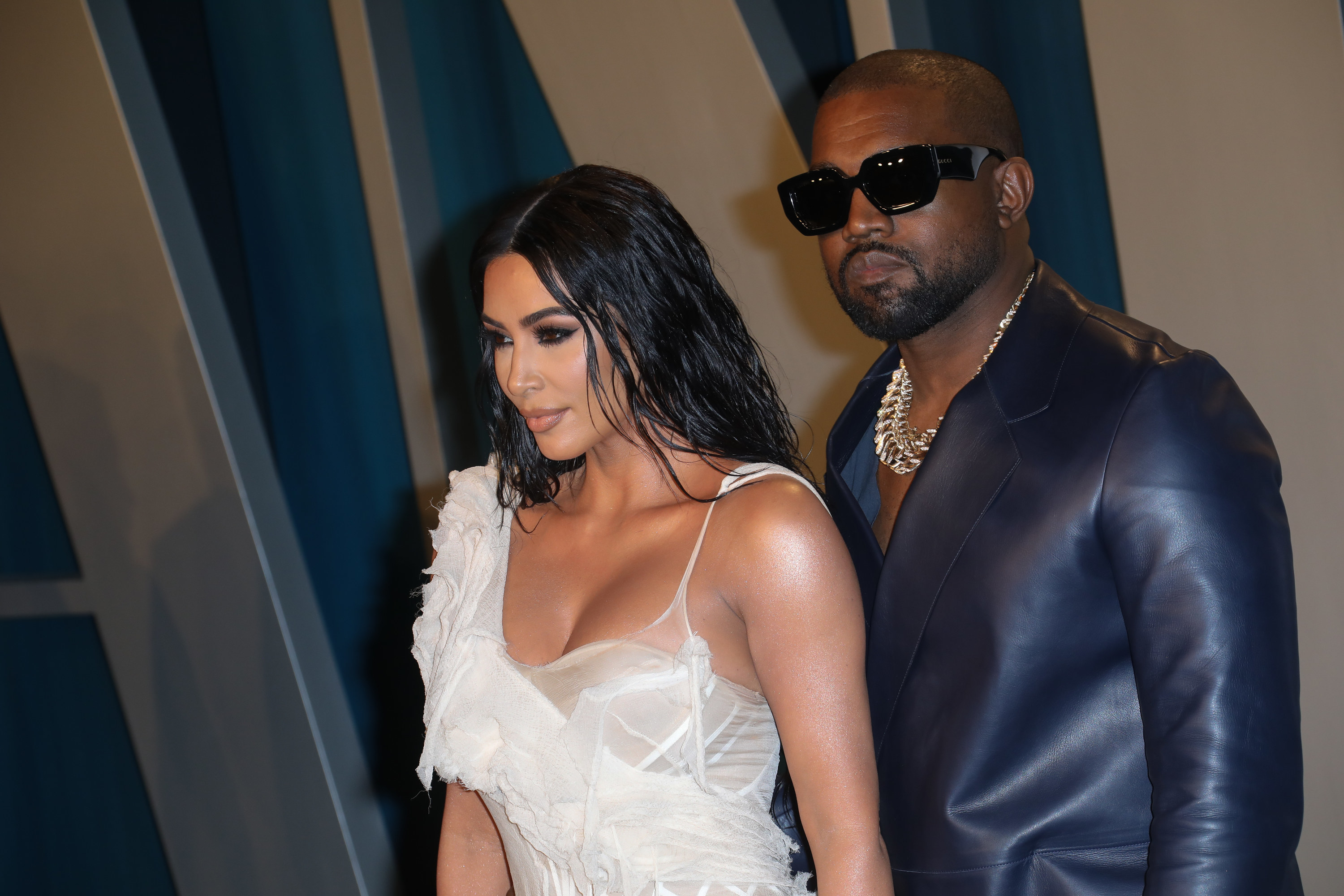 Photo of Kim Kardashian in a white gauzy dress with Kanye West in a leather suit and sunglasses