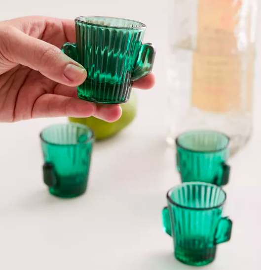 Someone holding up one of the cactus shaped shot glasses