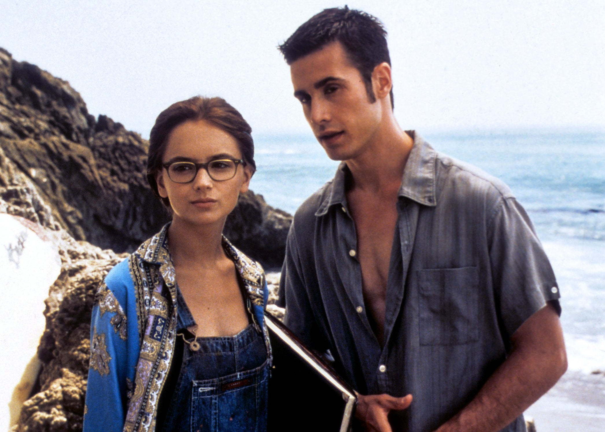 Rachael and Freddie stand on the beach in a shot from the movie