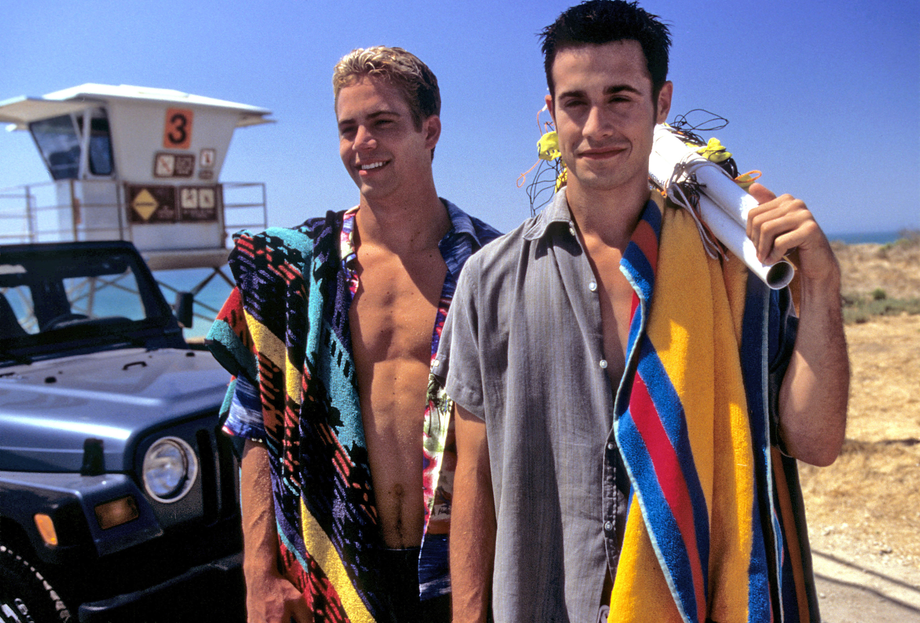Freddie and Paul stand next to each other on the beach and smile in a scene from the film