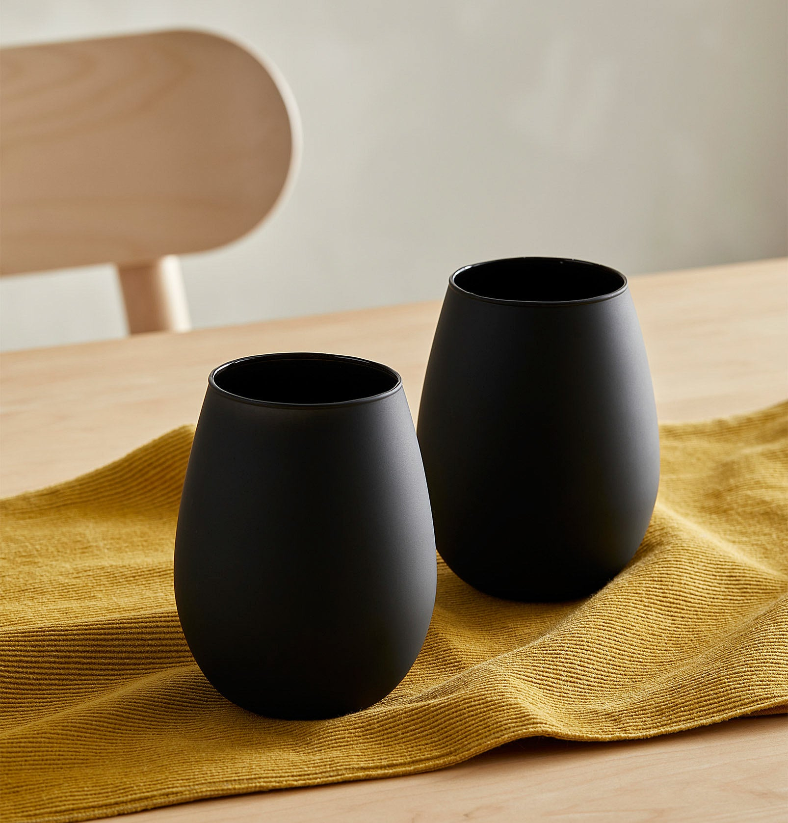 A pair of stemless matte wine glasses on a table