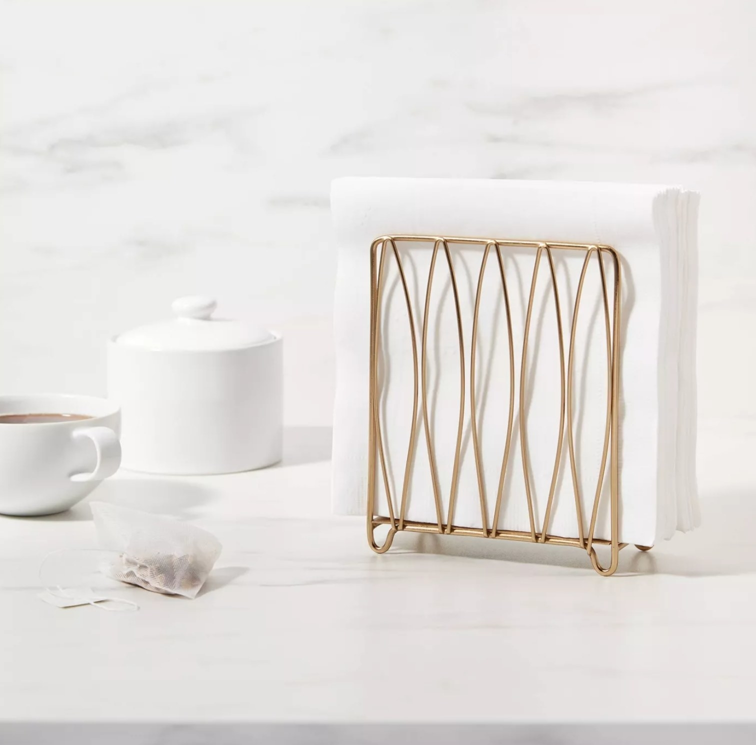 the gold napkin holder with white napkins in it on a counter next to a white mug with a tea bag beside it and a white canister.