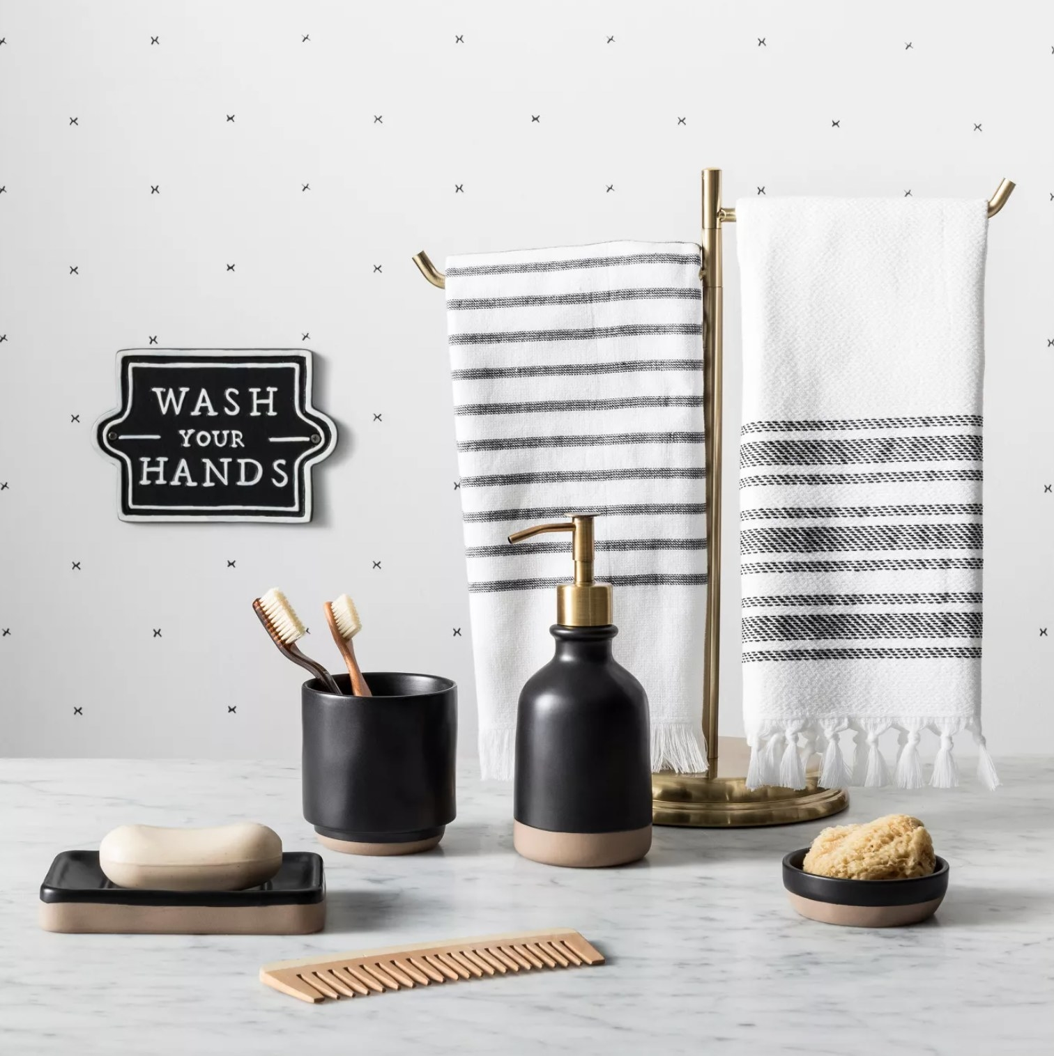 the black sign with white lettering hanging on a white wall with black dots over a counter with two towels hanging on a rack, a soap dispenser, soap dish, comb, toothbrush holder, and sponge holder all below it.
