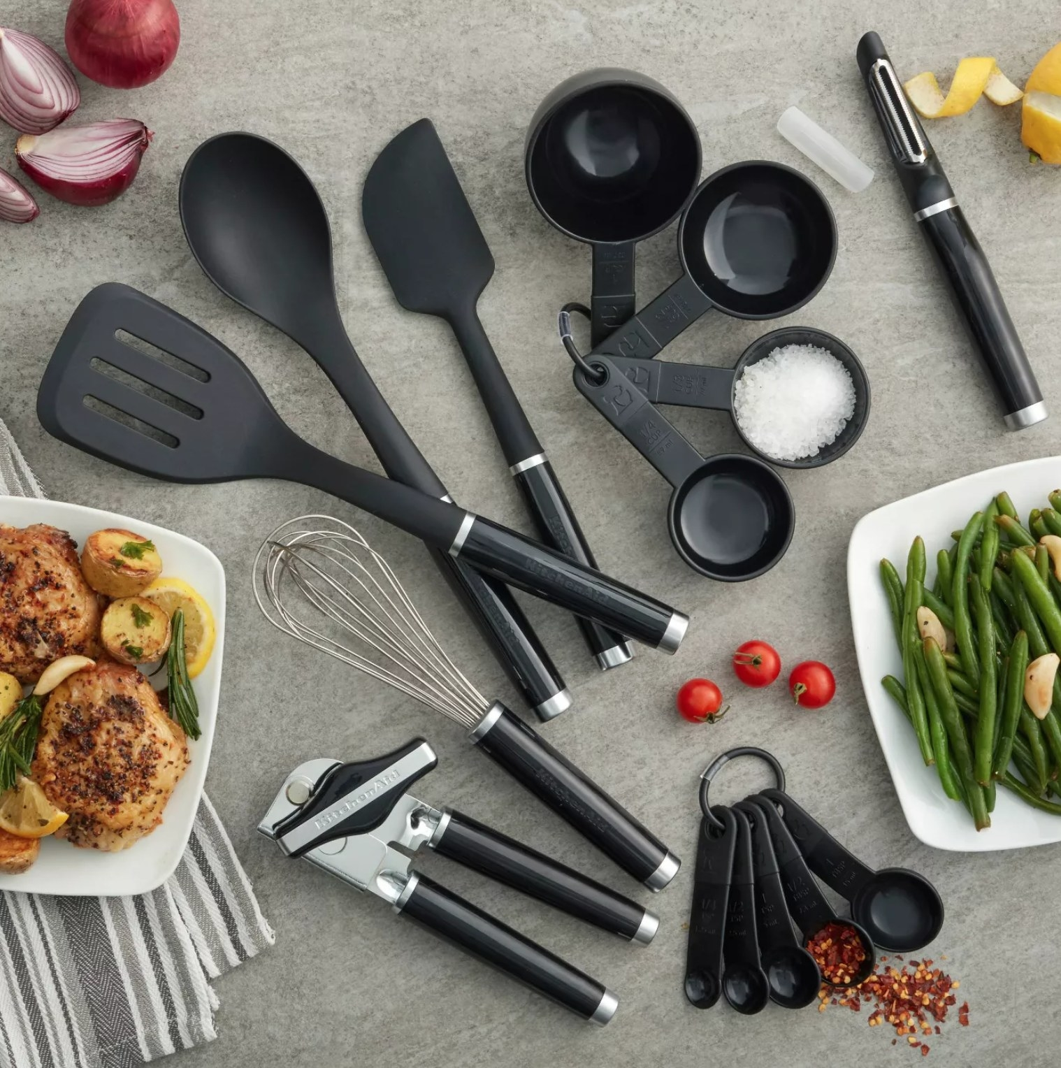 the utensil set on a gray counter with various plates of food and spices surrounding it.