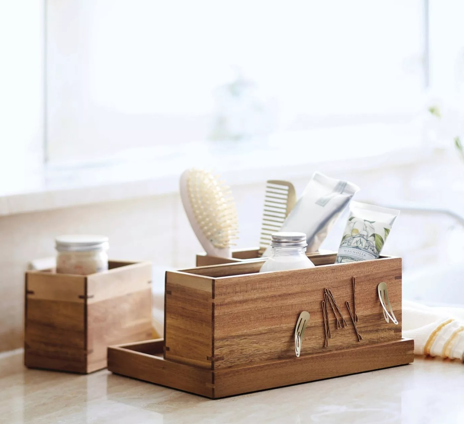 the wooden organizer with different bathroom essentials in it like brush, toothpaste, comb, and clips attached to the magnetic strip on the side