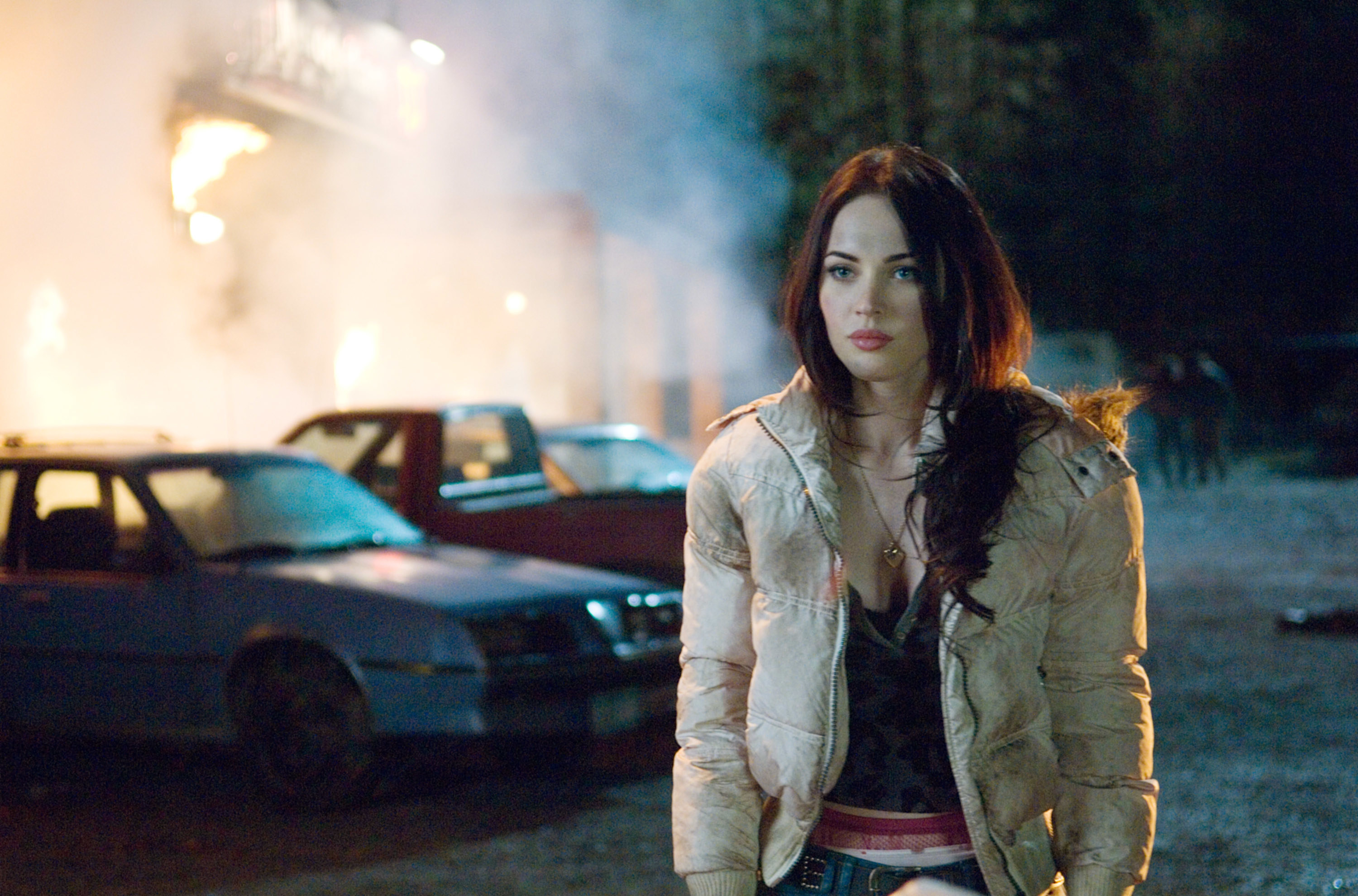 Megan Fox stands in front of a burning building