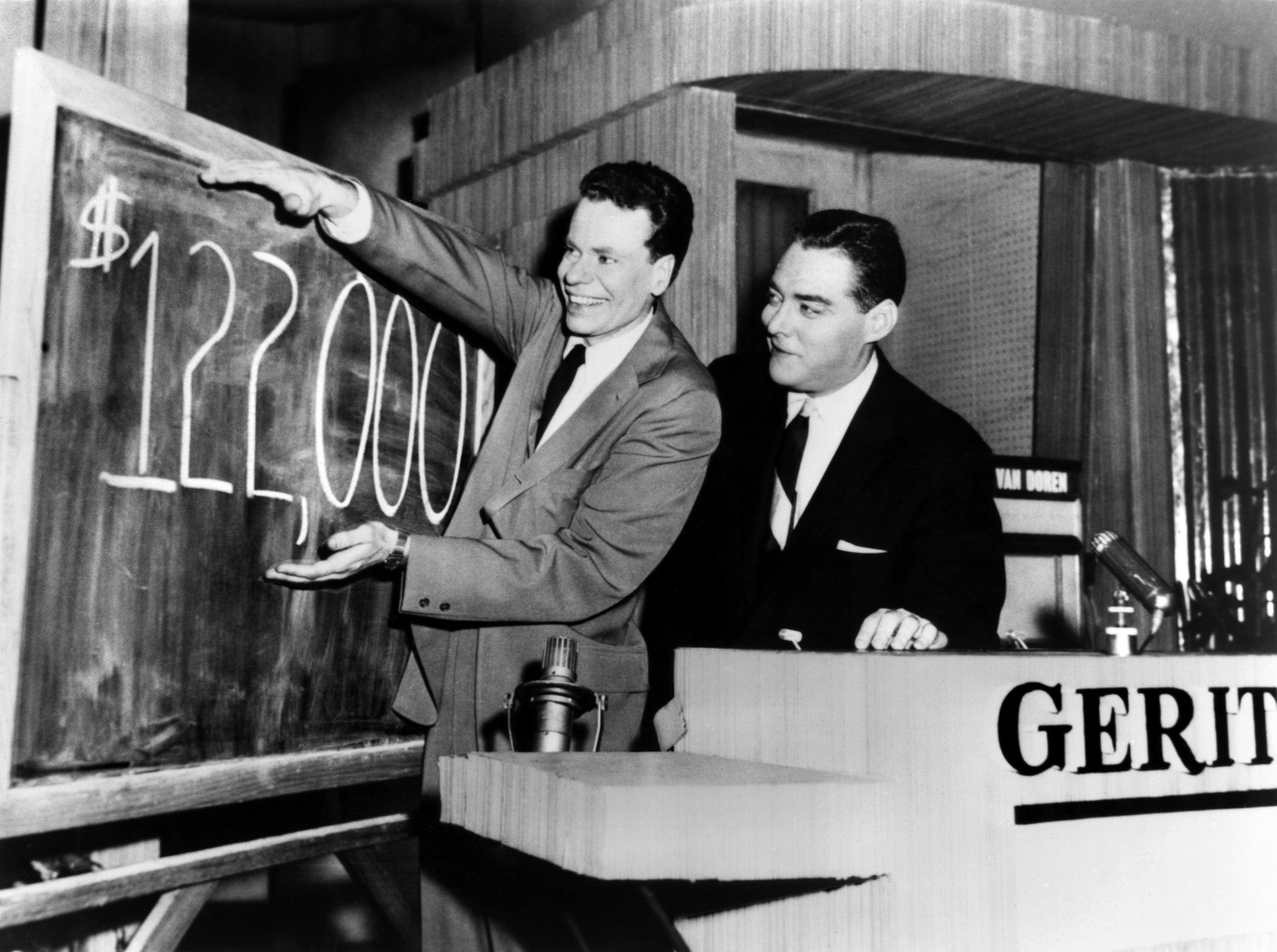 Van Doren standing next to a blackboard displaying his winnings, which were at that point $122,000
