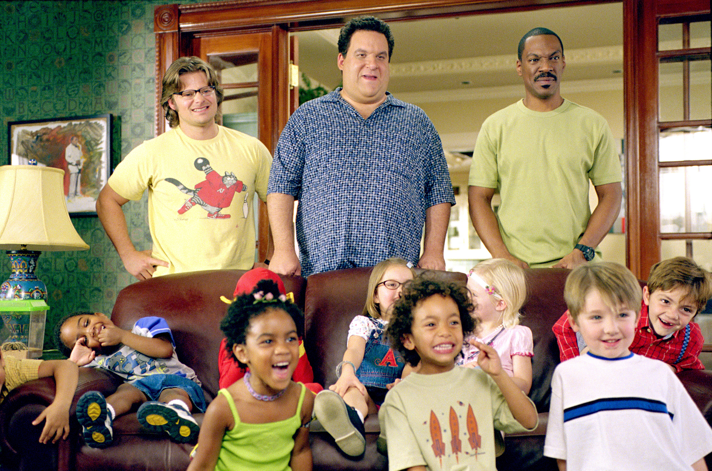 Steve Zahn, Jeff Garlin, and Eddie Murphy stand in front of a couch full of kids