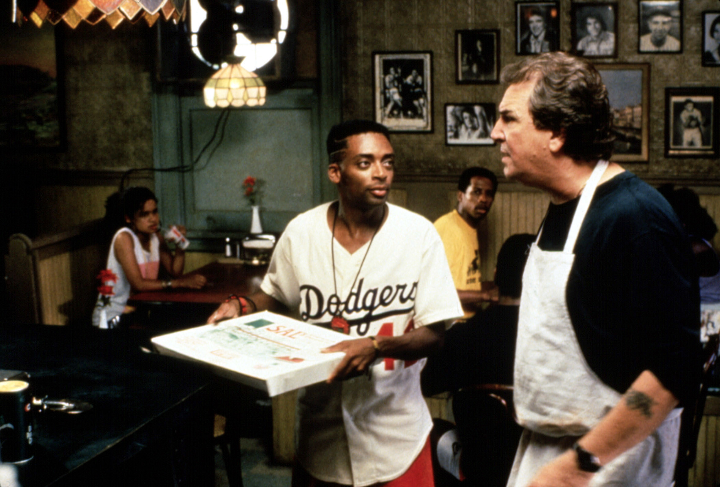 Spike Lee stands with a a pizza box talking to Danny Aiello