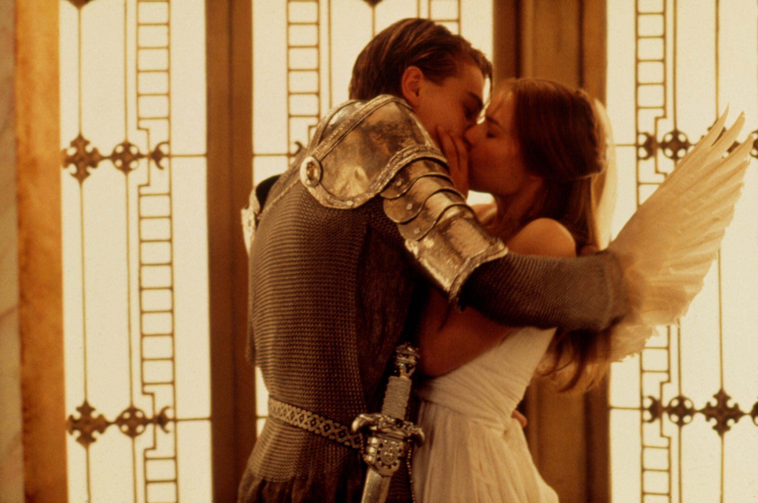 Leonardo Di Caprio dressed as a knight kisses Claire Danes dressed like an angel