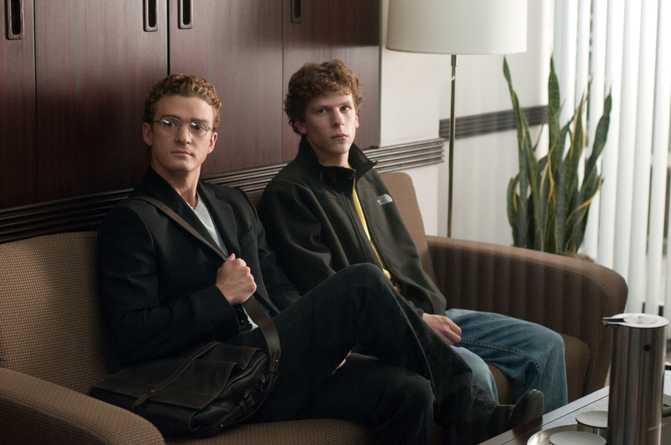 Justin Timberlake and Jesse Eisenberg sit on a couch