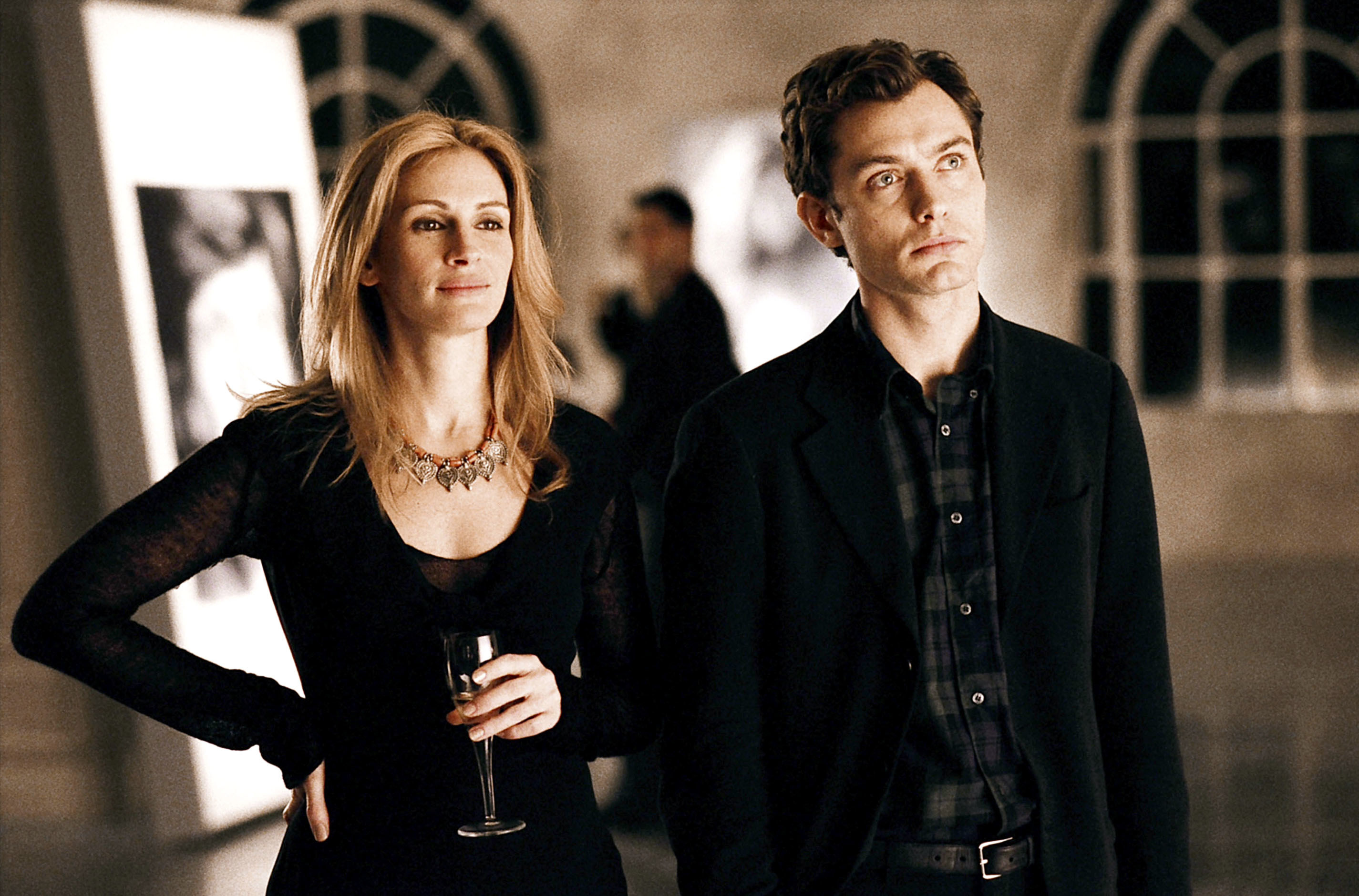 Julia Roberts and Jude Law look at a piece of art work