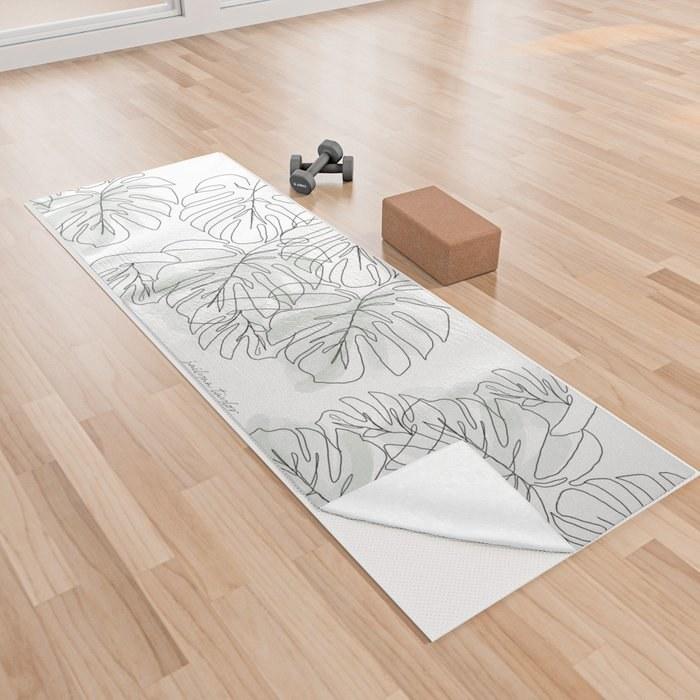 white yoga towel with botanical leaf design on top of white yoga mat on floor