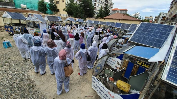 A crowd of women surrounded by their food carts, listens to Wajdi speak