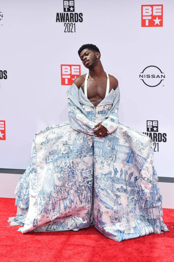Lil Nas poses on a red carpet in a printed off-shoulder ball gown