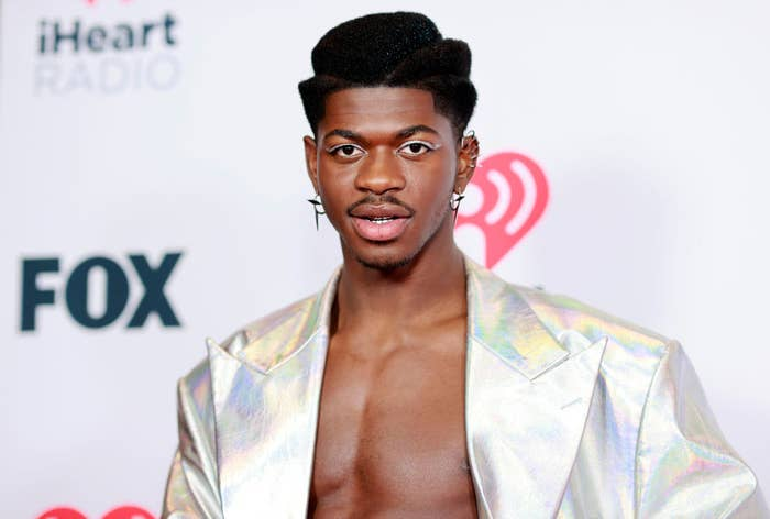 Lil Nas in a metallic jacket sans shirt with matching eyeliner and several earrings