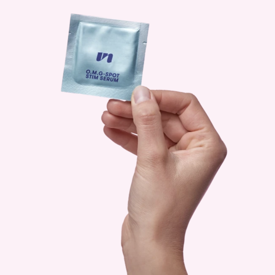 Model holding foil packet of O.M.G-Spot Stim Serum