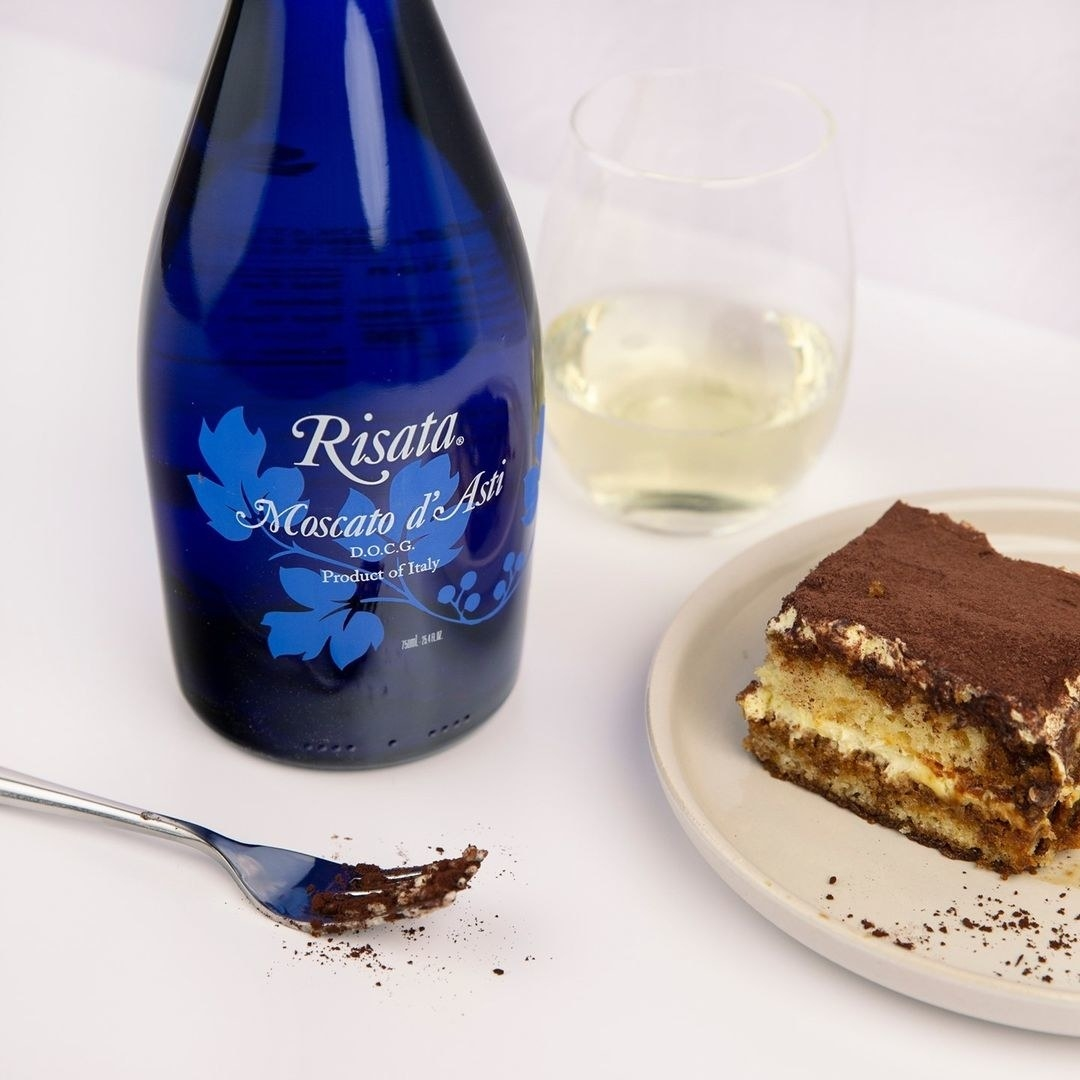 blue bottle of moscato next to a slice of tiramisu