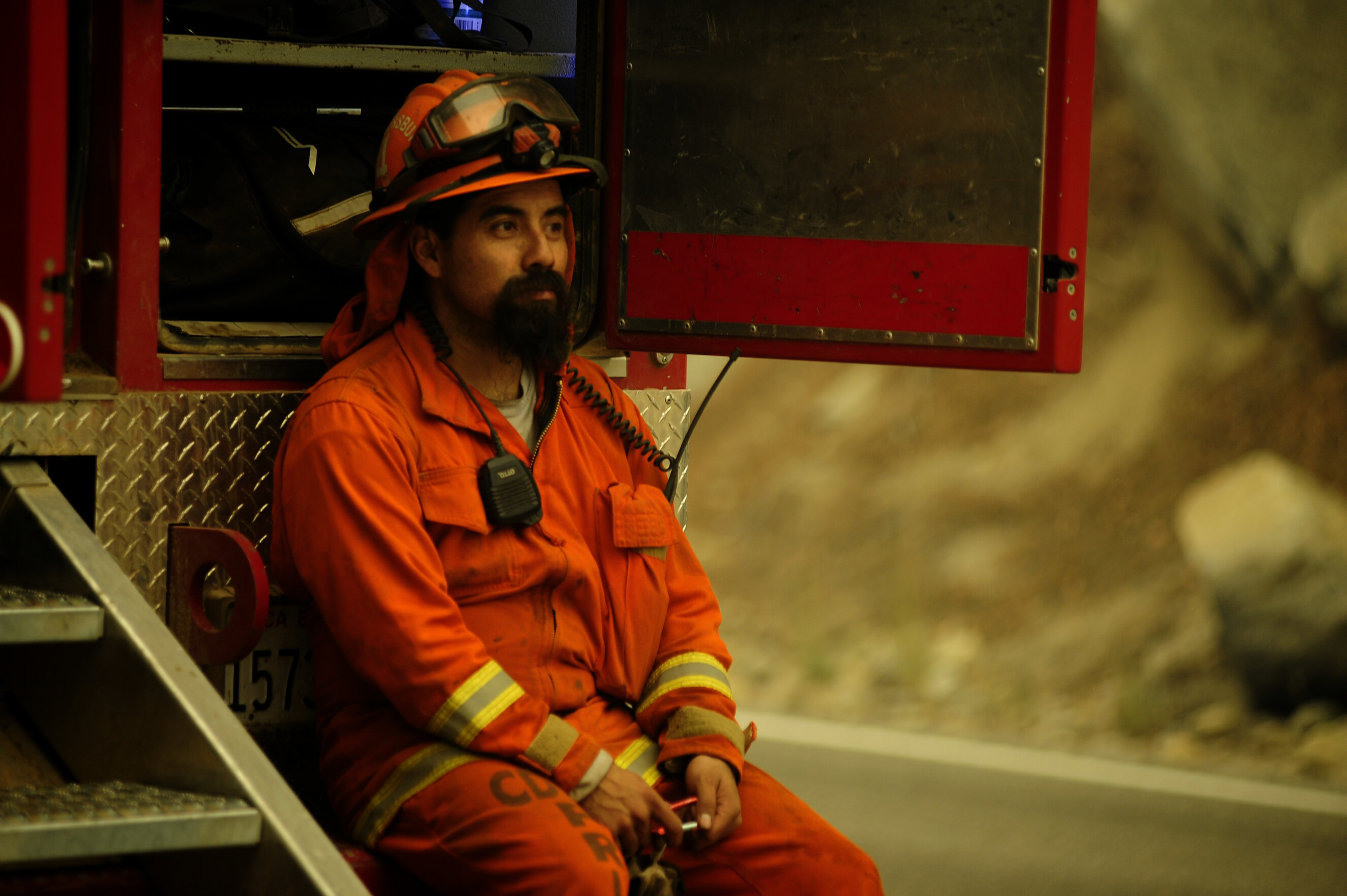 A firefighter in uniform sits on the back of a truck