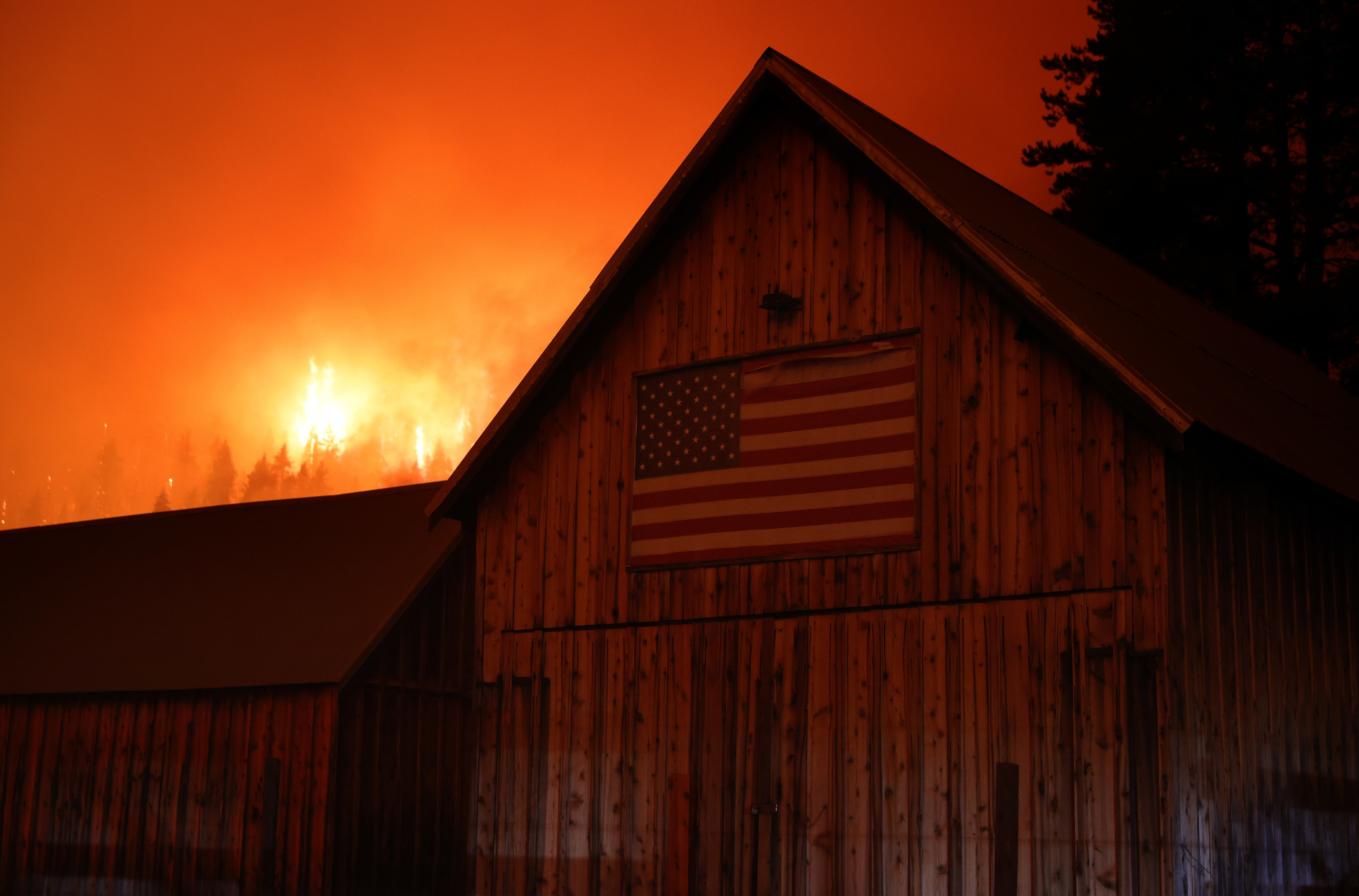 A fire blazes on a hillside in the background behind a barn with a US flag on the side