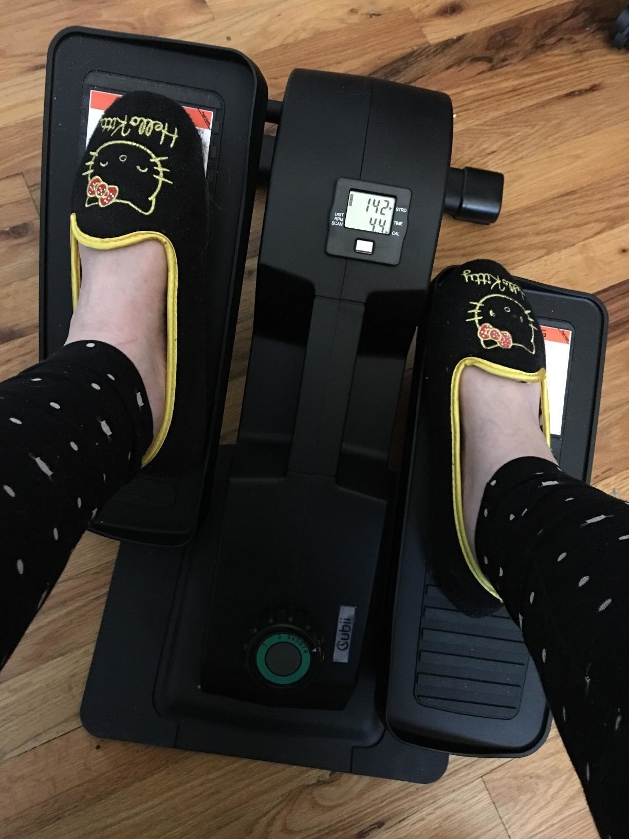 reviewer uses desk elliptical while wearing Hello Kitty slippers