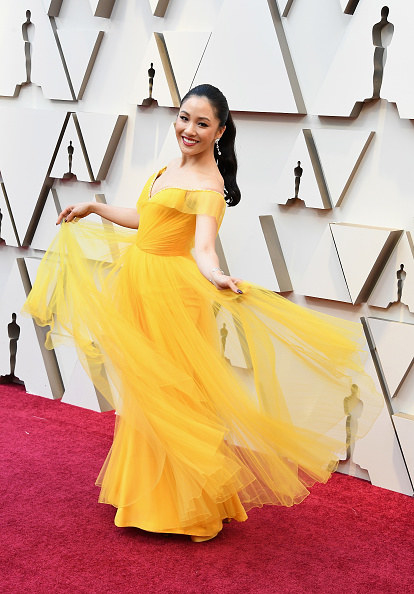 Constance Wu poses in a gauzy, bold gown