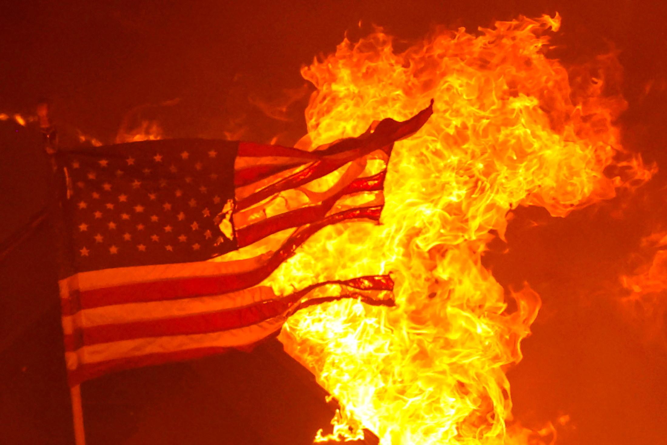A tattered US flag burns at night