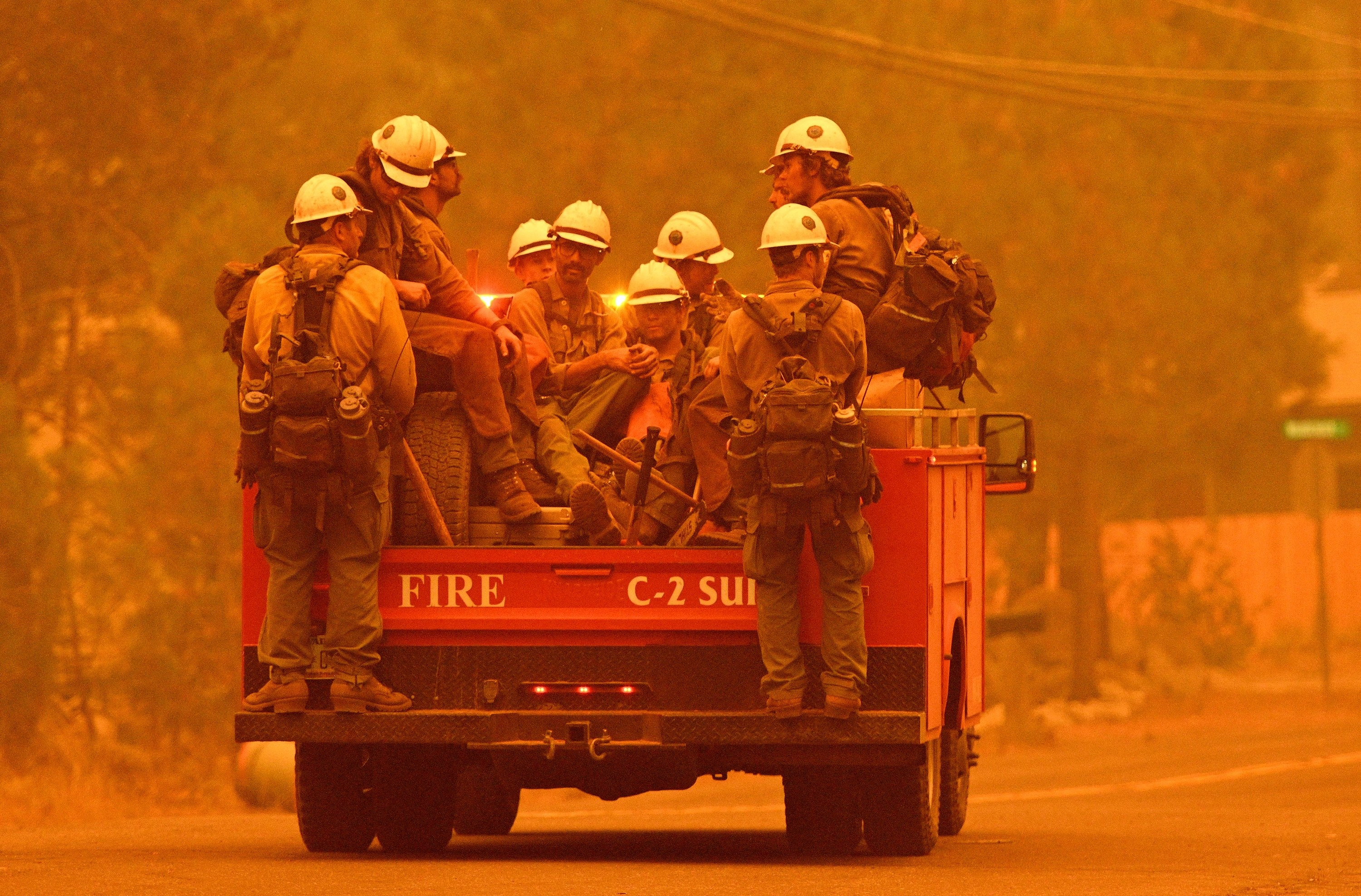 Ten firefighters in uniform sit and stand on a moving truck under a hazy sky