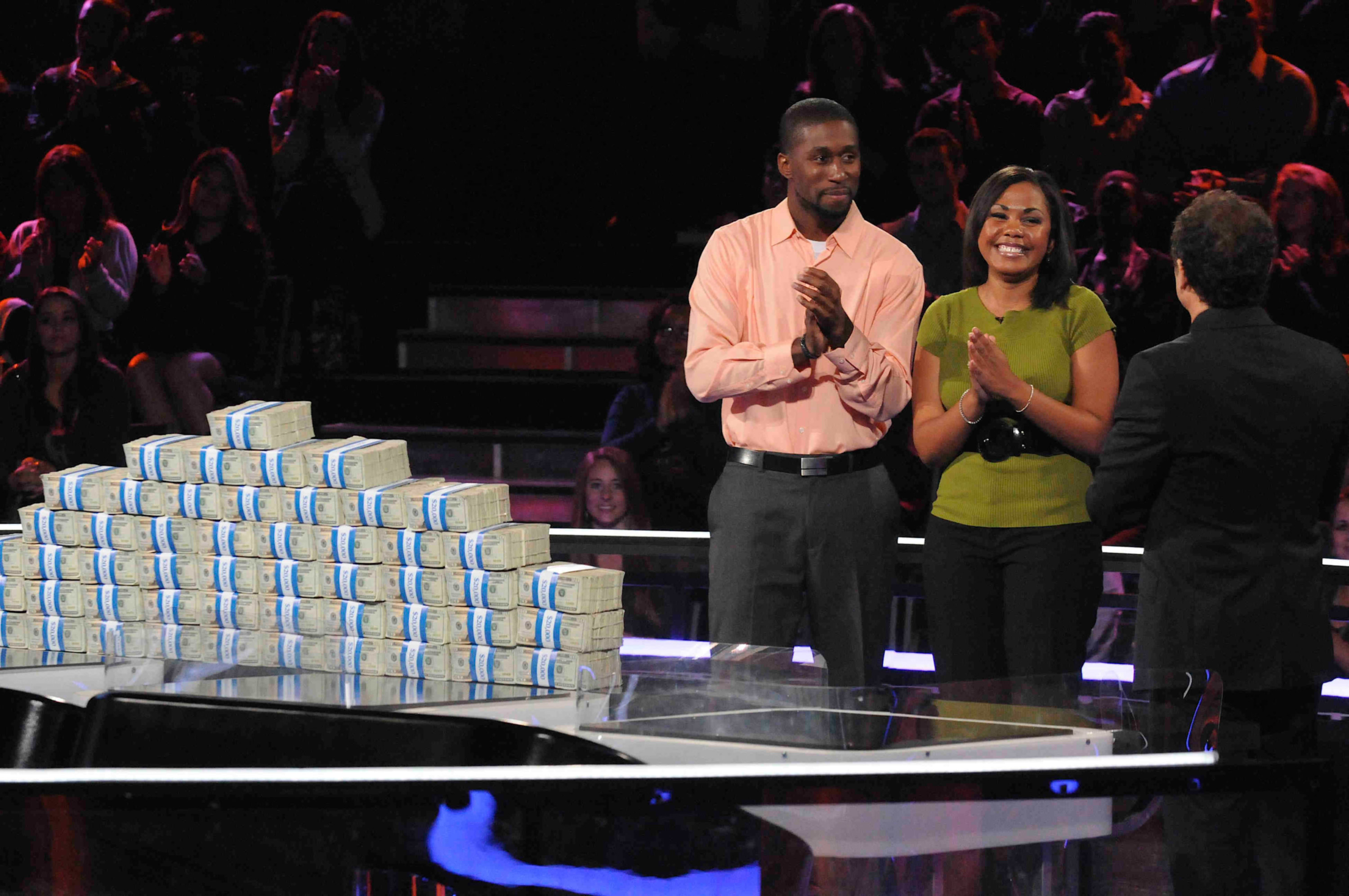 The two cheated contestants stand next to piles of money