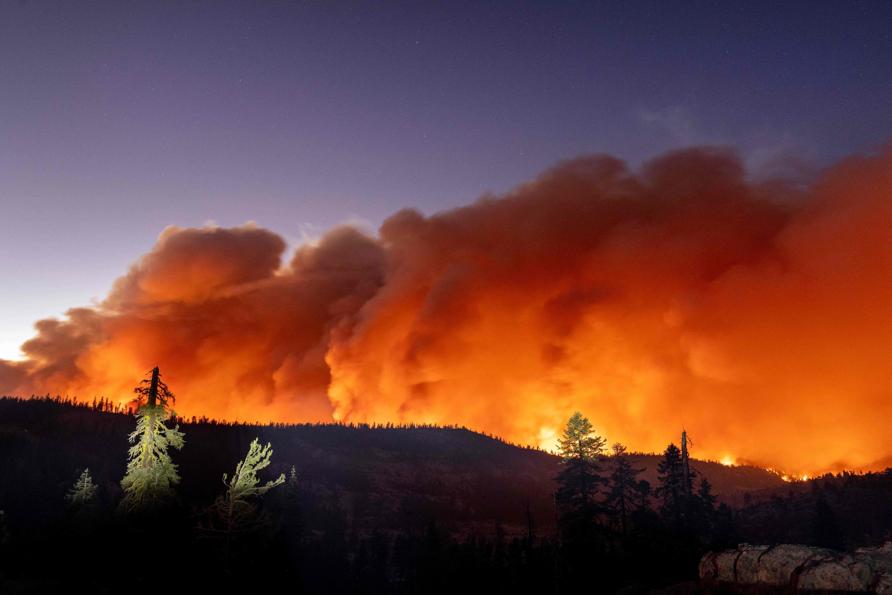 A massive cloud of smoke fills the sky over a forested ridge