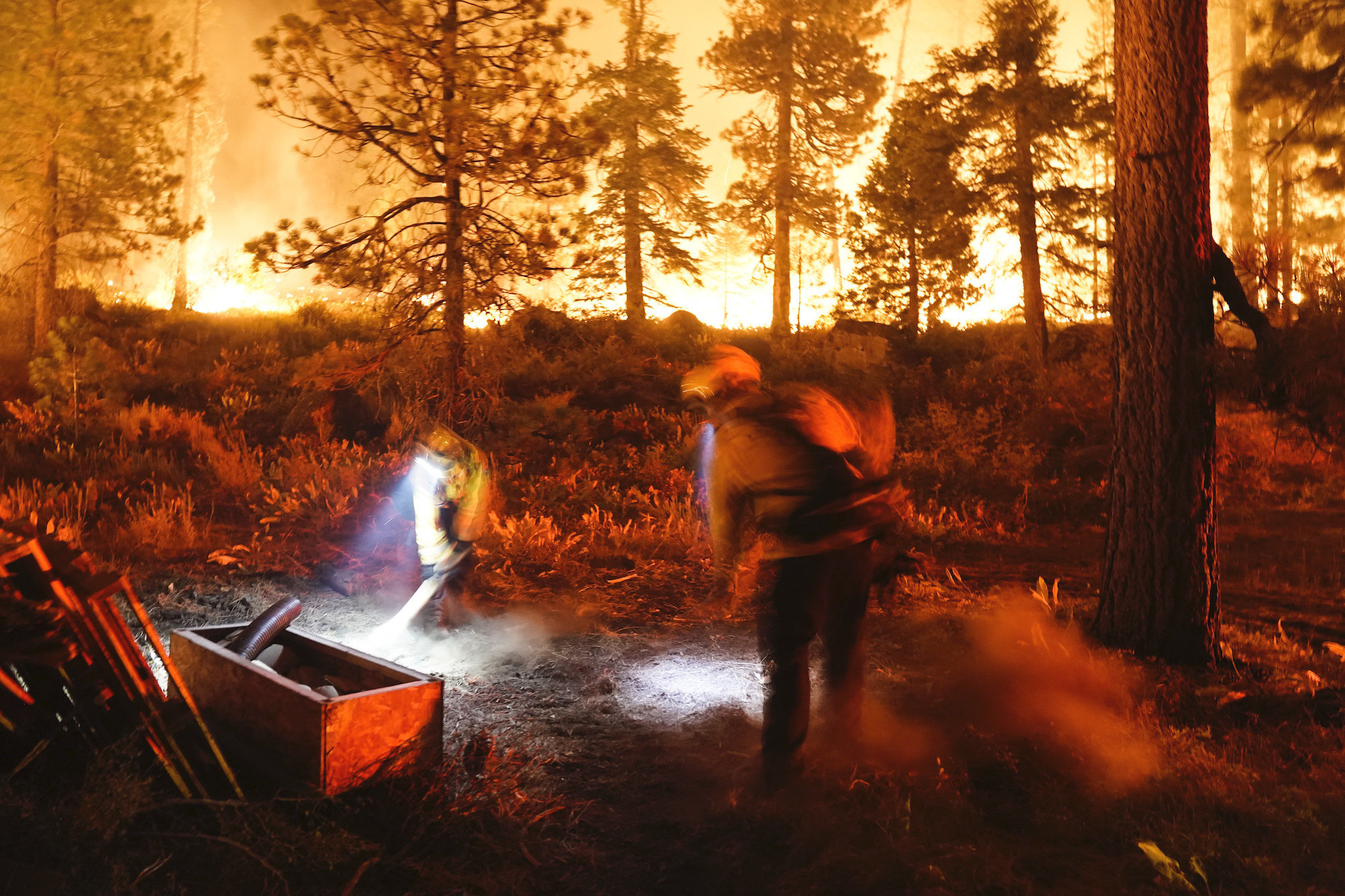 Two firefighters wearing gear and headlamps work at night in a burning forest