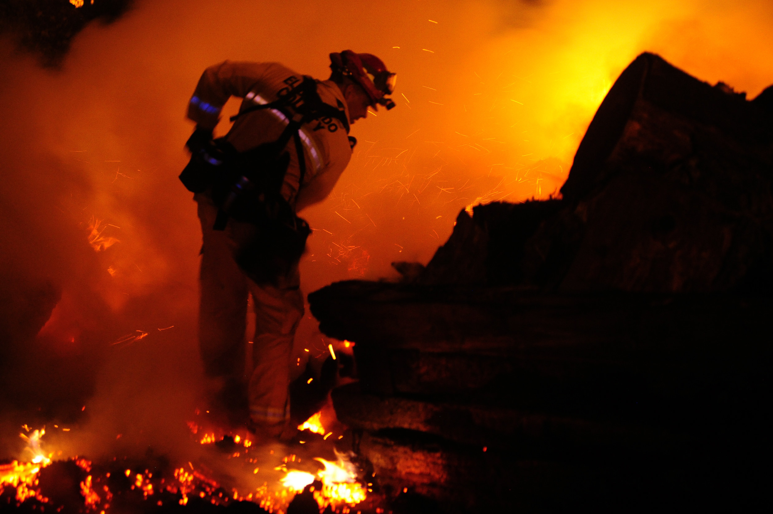 A firefighter stands on burning embers at night