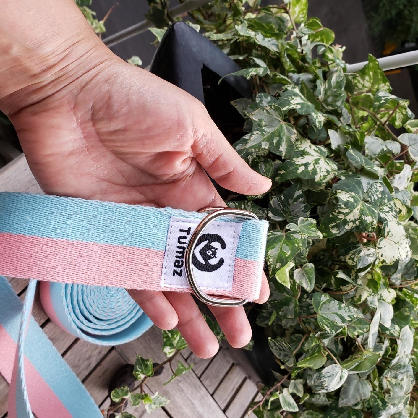 hand holds blue and pink yoga strap