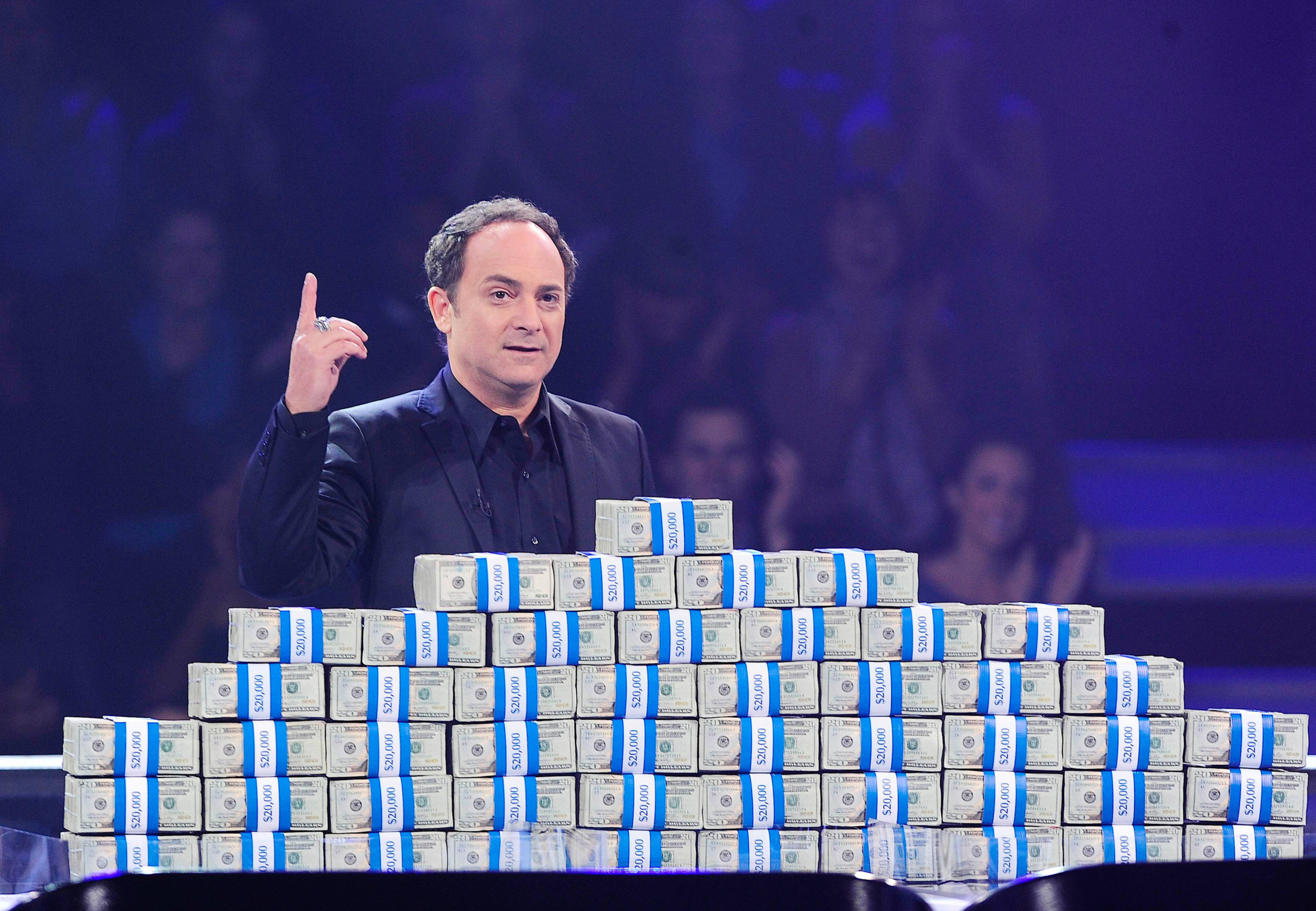 Kevin Pollak standing behind piles of cash