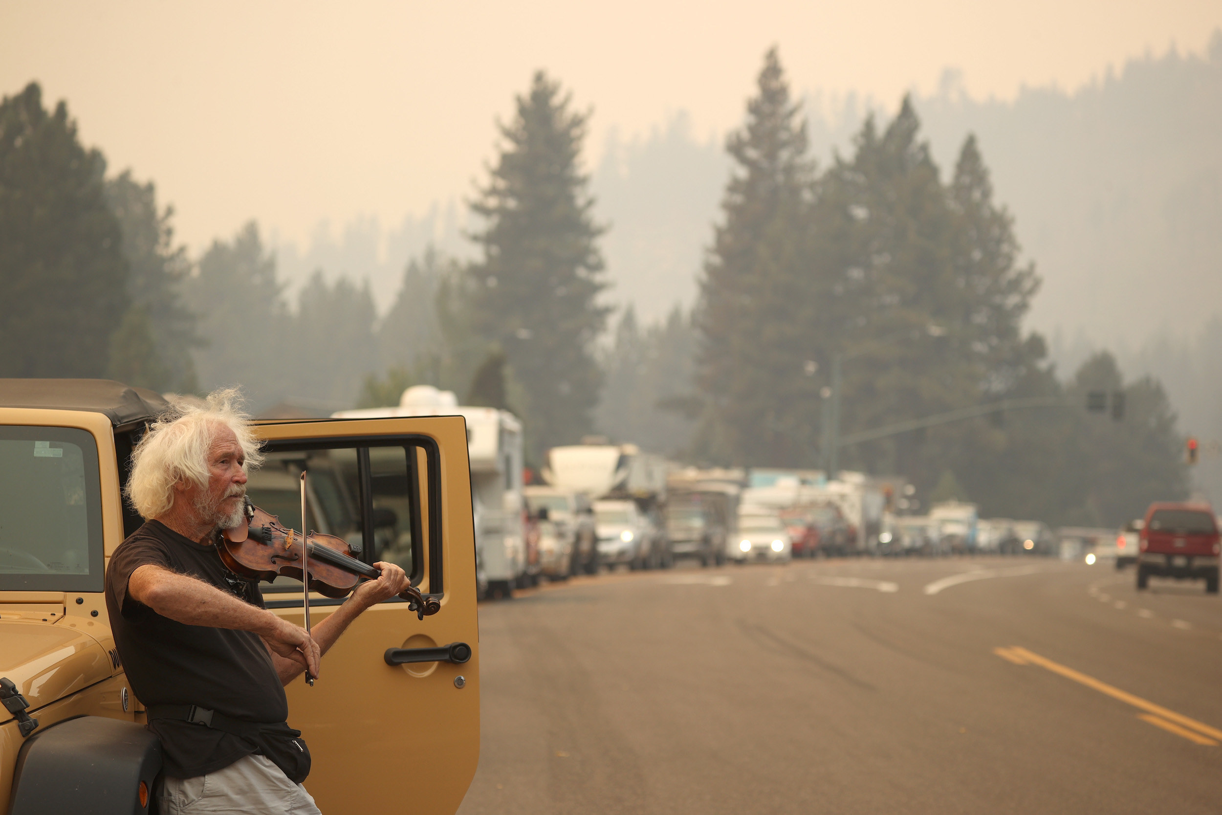 A man plays violin and leans against his Jeep in front of several cars in bumper-to-bumper traffic under a smoky sky