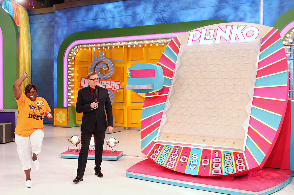 Drew Carey and a contestant next to the giant Plinko board