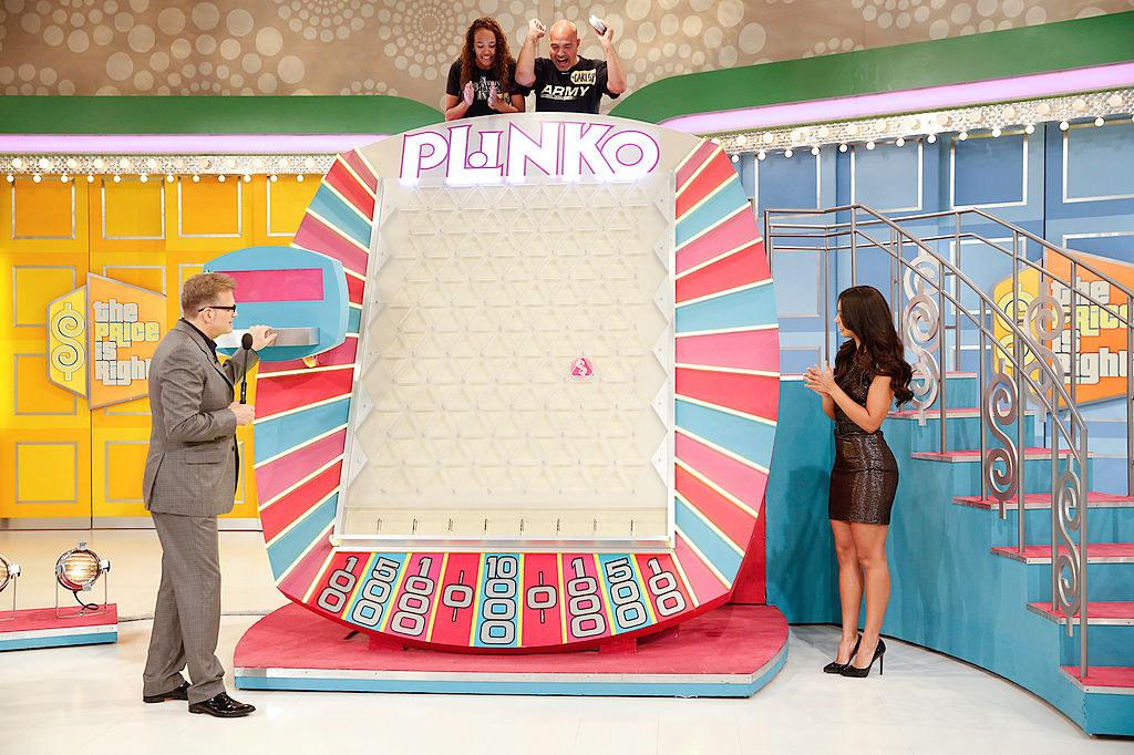 Drew Carey standing next to the massive Plinko board