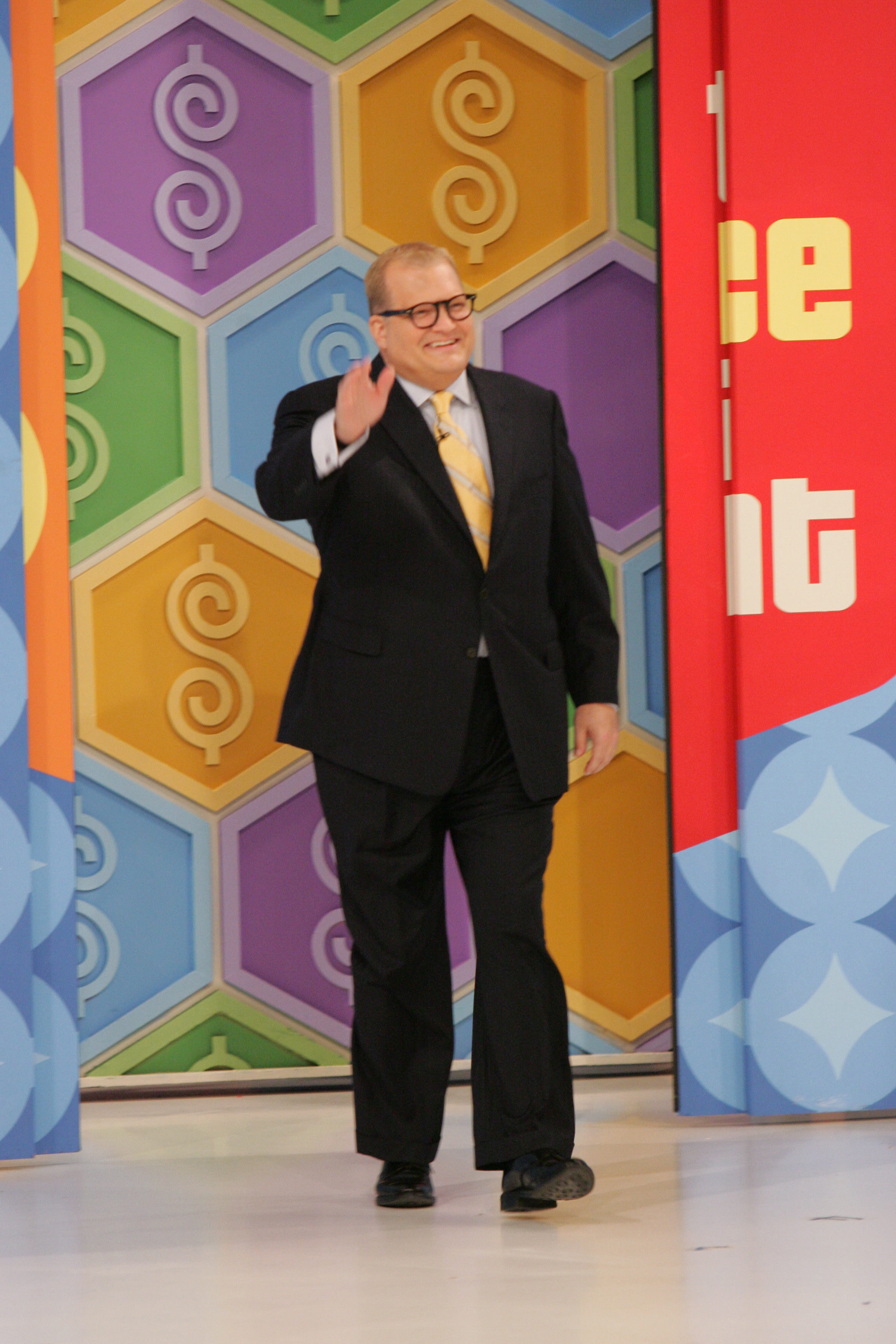 Drew Carey emerges waving from backstage