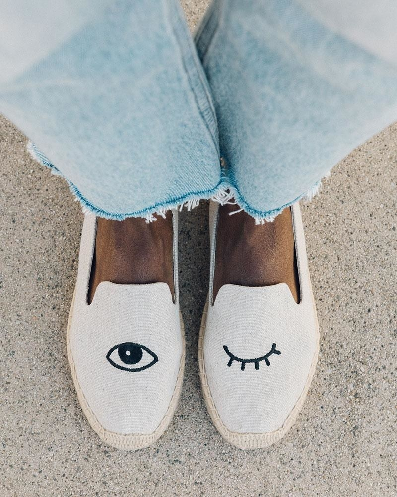 white espadrille with an open eye on the right shoe and a closed eye design on the left one
